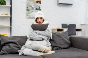 woman-huddled-on-couch-in-hat-and-blanket