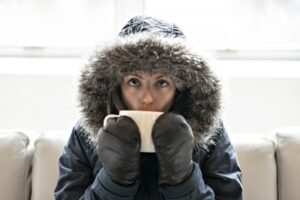 woman-wearing-parka-and-sipping-from-mug-on-couch