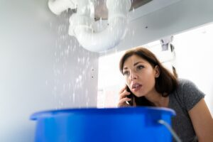 woman-watching-water-leak-from-pipe-under-sink