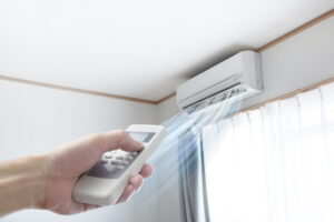 hand-with-remote-turning-on-ductless-air-handler